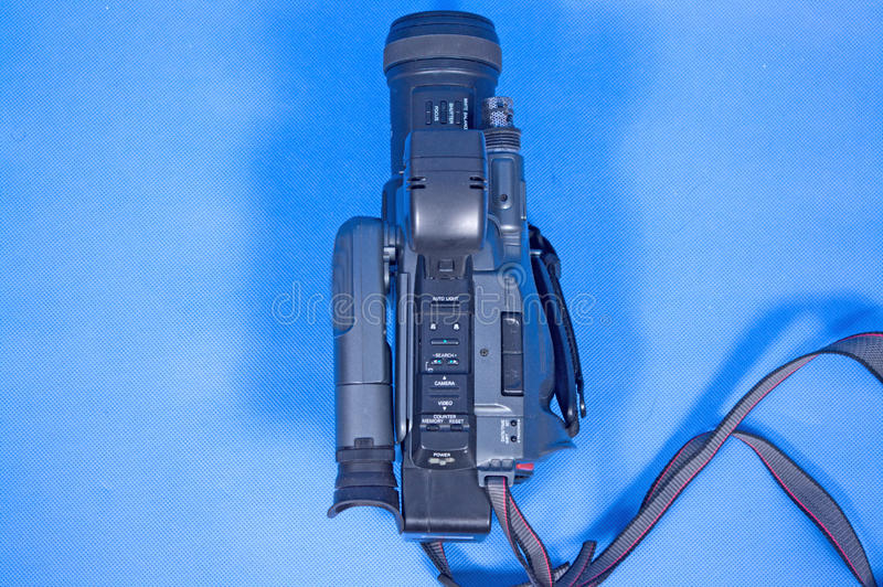 Analog video camera. On a blue background royalty free stock image