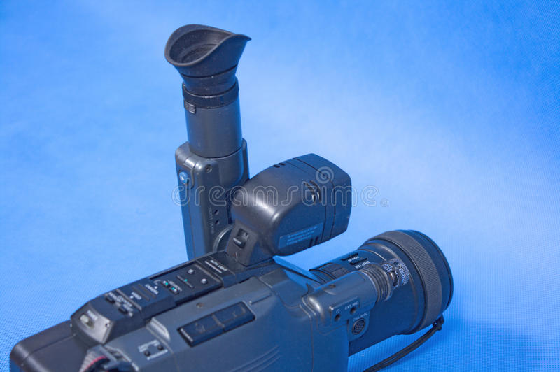 Analog video camera. On a blue background royalty free stock photography
