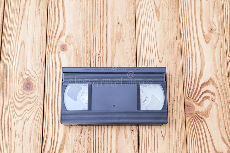 Analog video cassette on wooden background. Black analog video cassette on wooden background royalty free stock photography