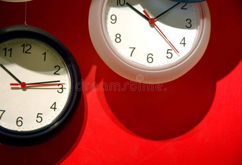 Analoge Borduhren auf roter Wand stockfotos