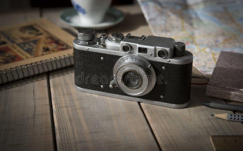 Analoge Filmkamera der Weinlese auf einem Holztisch, Karte, Notizblock, Bleistift stockfotografie