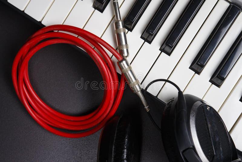 Analoge Niveaus Musikinstrumentnahaufnahme auf schwarzem Hintergrund Synthesizer, Kopfhörer und Kabel Midi-Schlüssel und Steckfas stockfotografie