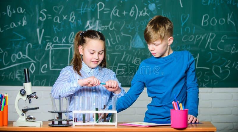 Analyse chimique Chimie occup?e d'?tude d'enfants Le?on de chimie d'?cole Laboratoire d'?cole Décrivez la réaction chimique photos libres de droits