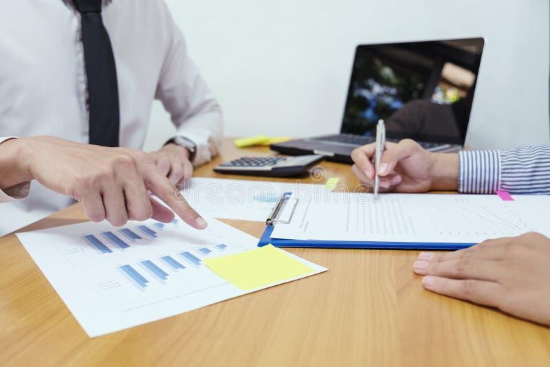Analyse d'homme d'affaires sur le papier de données avec la femme d'affaires sur le bois images stock