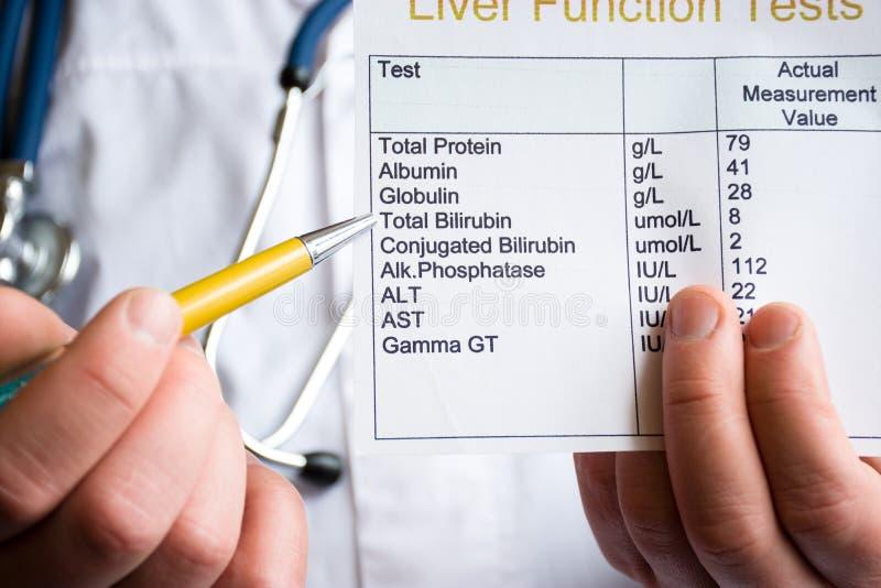 Analyse de photo de concept de bilirubine Soignez tenir l'essai en laboratoire de la fonction hépatique et indiquez le stylo bill images stock