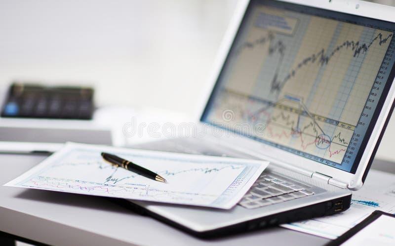 Analyse des diagrammes d'investissement avec l'ordinateur portable photo libre de droits