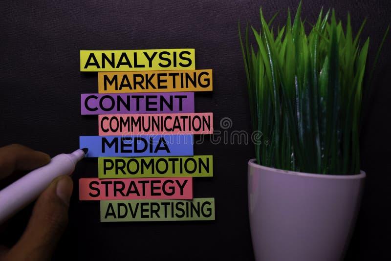 Analyse, Marketing, Inhoud, Mededeling, Media, Bevordering, Strategie, Reclametekst van kleverige nota's die op Zwart bureau word stock afbeeldingen