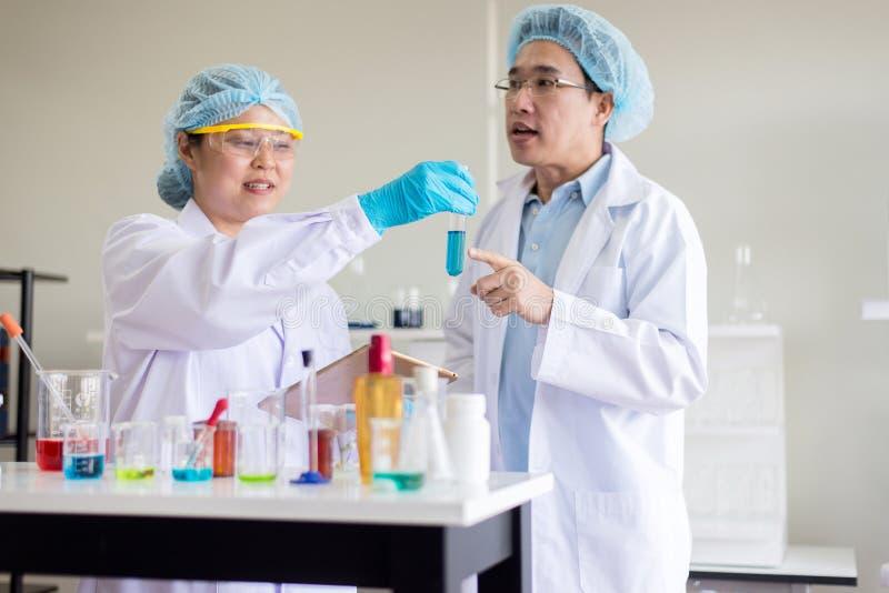 Analyse travaillante de scientifique remontant l'échantillon médical de produits chimiques dans le tube à essai au laboratoire photographie stock libre de droits