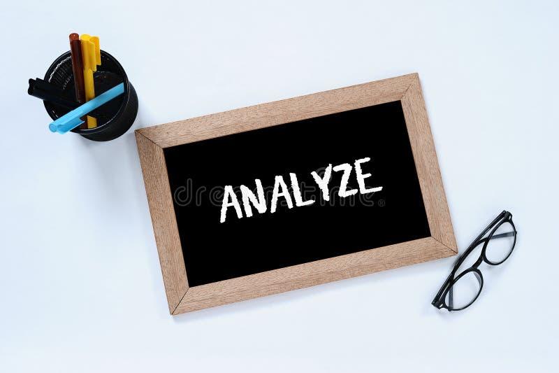 Analysera - det isolerade ordet i b?sta sikt av svart tavla Aff?ren analyserar f?r att f? m?l Exponeringsglas-, mark?r- och pennf arkivfoto