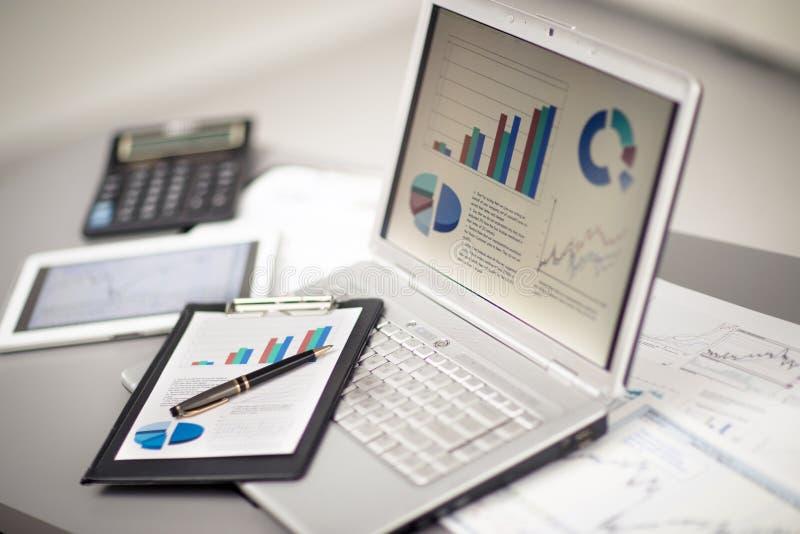 Analysering av investeringdiagram med bärbara datorn royaltyfri fotografi