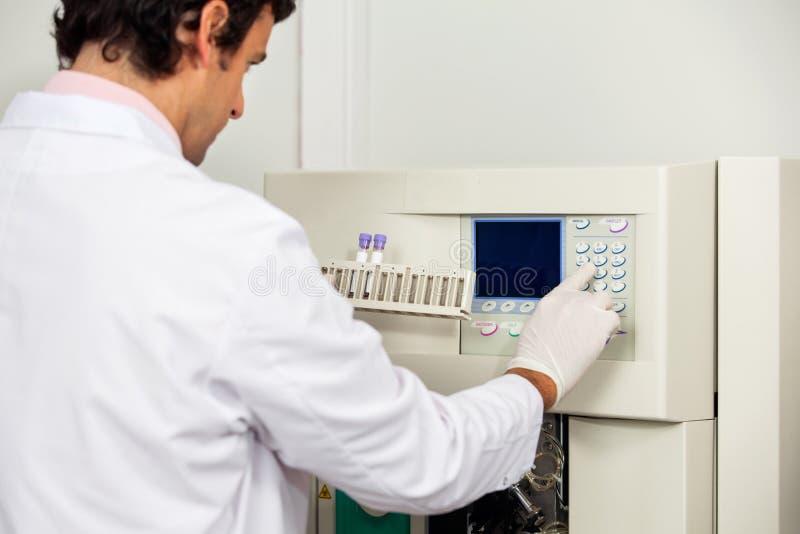 Analyseur de With Samples Operating de scientifique dans le laboratoire image stock