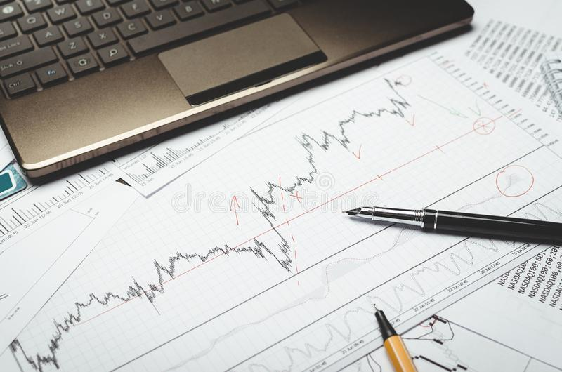 Analysis of financial charts on paper, pen and laptop royalty free stock image