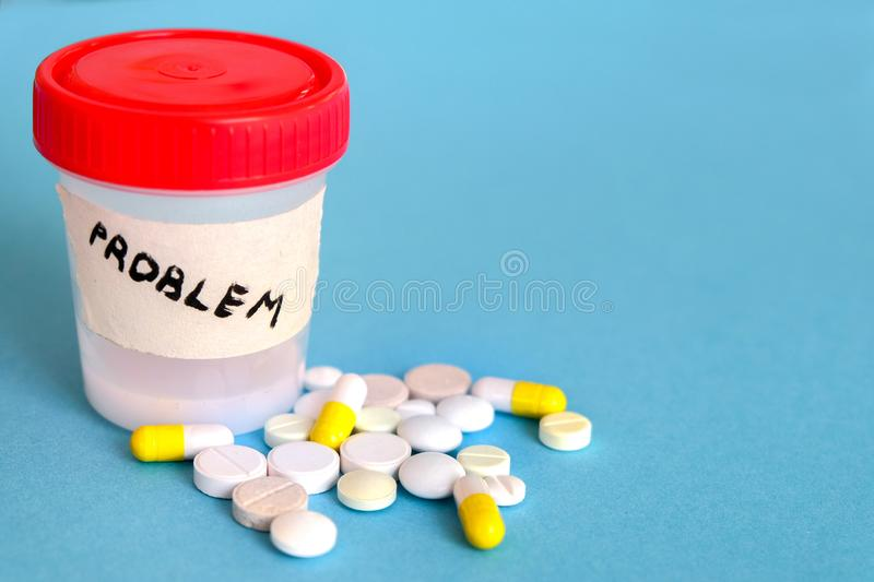 Analysis jar with a red cap with the inscription Problem stands on a blue background. Nearby are pills stock image