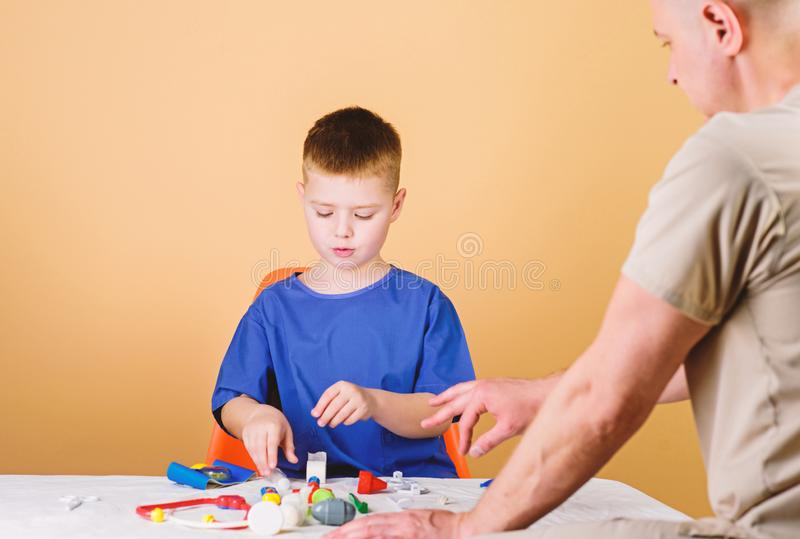 Analysis laboratory. Kid little doctor sit table medical tools. Health care. Pediatrician concept. Medical examination. Boy cute child and his father doctor stock image