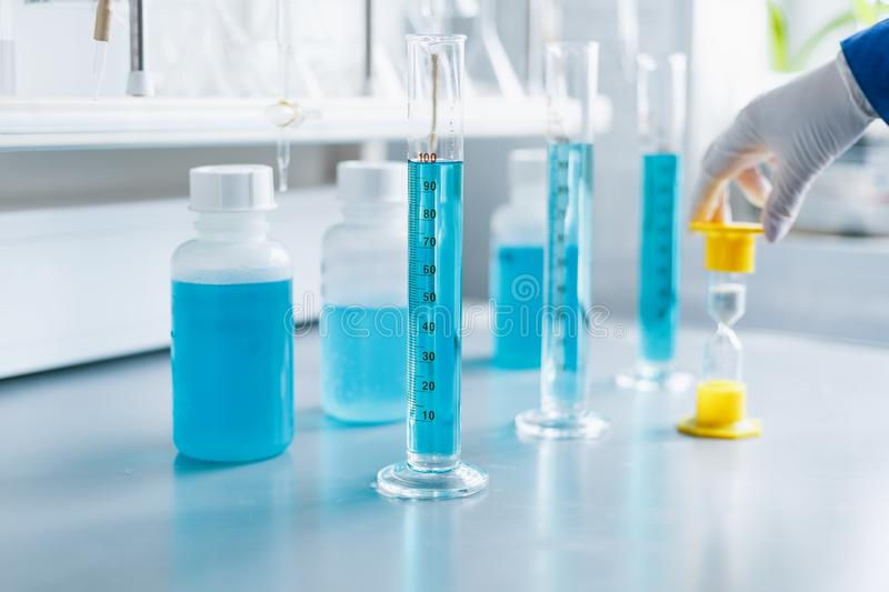 Analysis of the quality of liquids in a chemical laboratory, a device with equipment made of glass with a blue liquid. The hands of a scientist with close-ups royalty free stock images