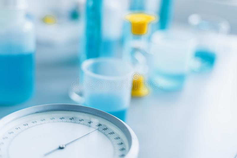 Analysis of the quality of liquids in a chemical laboratory, a device with equipment made of glass with a blue liquid. The hands of a scientist with close-ups stock image