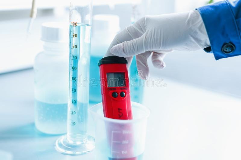 Analysis of water quality in a chemical laboratory, a device for measuring pH with equipment made of glass. The hands of a scientist with a red pH meter close stock images