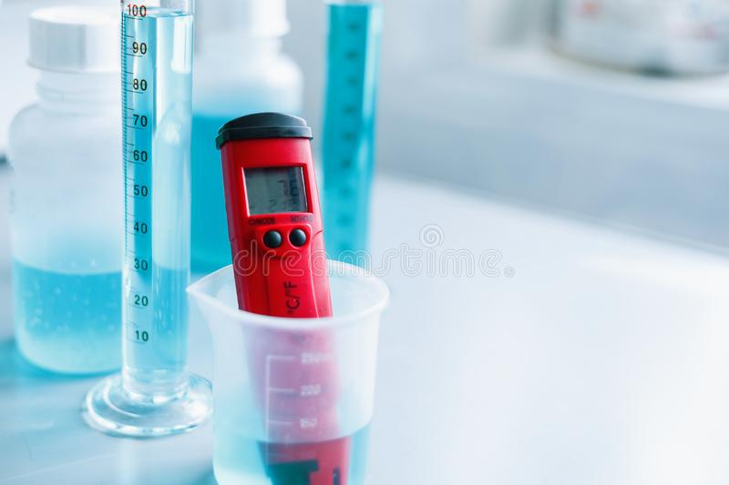 Analysis of water quality in a chemical laboratory, a device for measuring pH with equipment made of glass. The hands of a scientist with a red pH meter close royalty free stock image