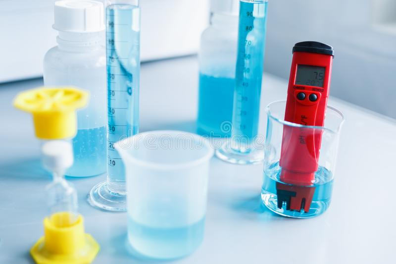 Analysis of water quality in a chemical laboratory, a device for measuring pH with equipment made of glass. The hands of a scientist with a red pH meter close royalty free stock photos