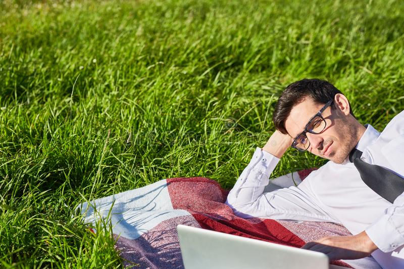 Analyst working. Serious young businessman lying on lawn in front of laptop and analyzing online data royalty free stock photography