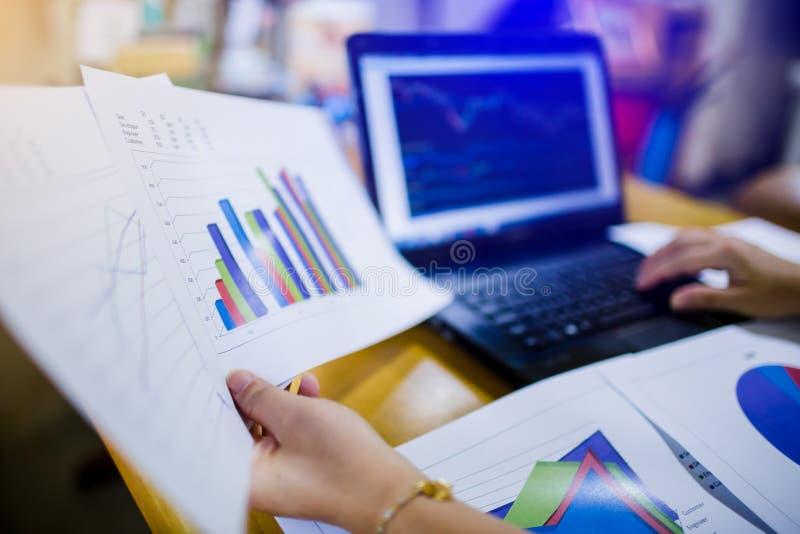 Analyste de marché de finances de femme travaillant sur l'ordinateur portable tout en se reposant à la table en bois photos libres de droits