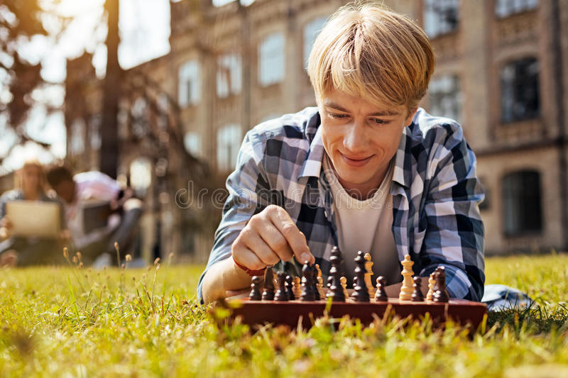 Analytical intelligent man relaxing while playing. Calculating the moves. Lively motivated productive guy training his cognitive abilities by developing game stock photo