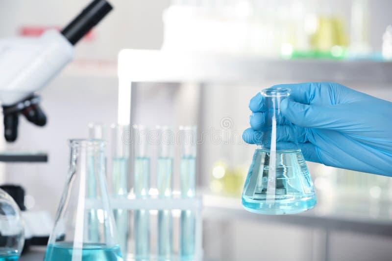 Analytiker, der Flasche mit Flüssigkeit im laborator hält lizenzfreies stockfoto