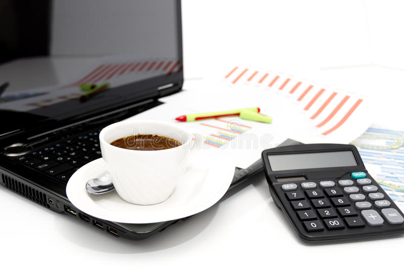 Analyzing business investment charts with calculator and laptop. Photo of the Analyzing business investment charts with calculator and laptop stock photography