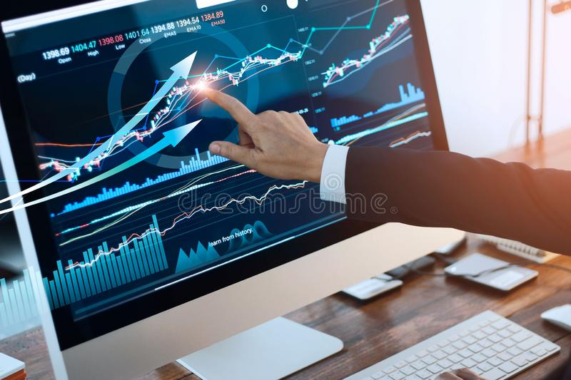 Analyzing data. Hand of businessman touching graph and chart stock market on screen in work place.  royalty free stock photos