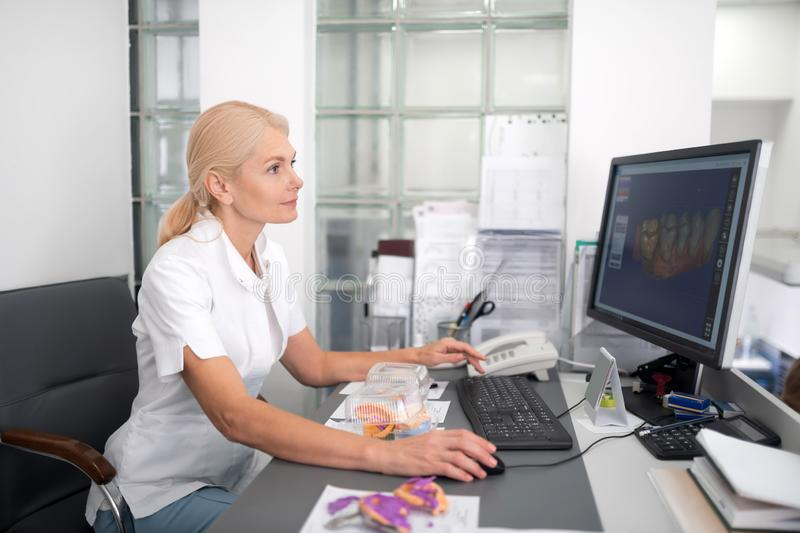 Dentist looking at the picture of teeth. Analyzing the dental structure. Smiling dentist sitting in front of her computer looking at the picture of teeth there stock images