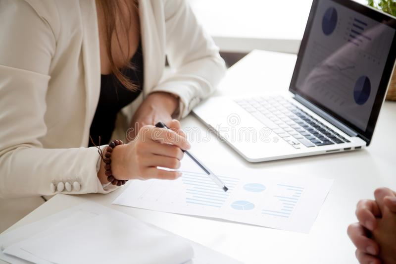 Analyzing new marketing plan and sales statistics concept, close. Businesswoman discussing new marketing plan analyzing sales statistics with laptop documents at royalty free stock photography
