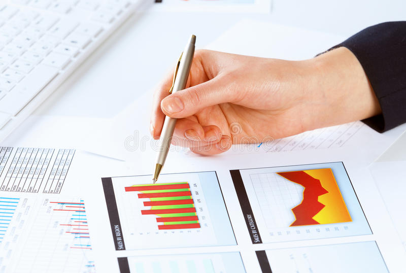 Analyzing report. Close up of male hand holding pen and pointing at graphs stock image