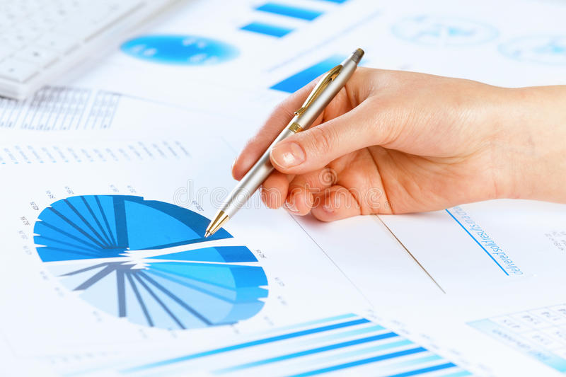 Analyzing report. Close up of male hand holding pen and pointing at graphs stock photos