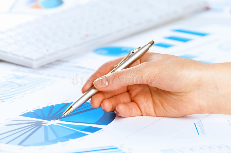 Analyzing report. Close up of male hand holding pen and pointing at graphs stock photography