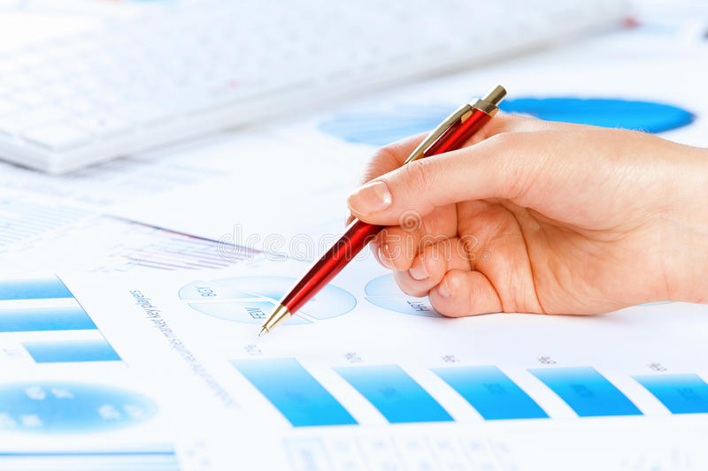 Analyzing report. Close up of male hand holding pen and pointing at graphs stock photo