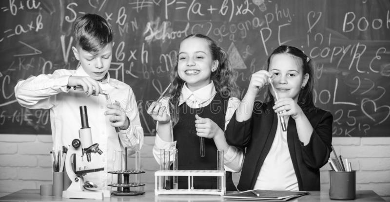 Analyzing strategy. Little children at laboratory. Little kids learn chemistry in school lab. Chemistry microscope royalty free stock photo