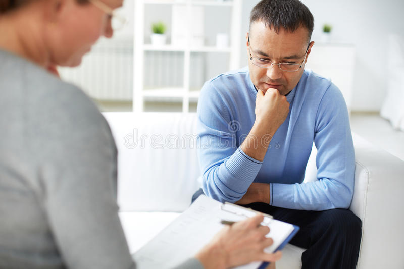 Anamnesis. Man sharing problems with psychologist stock image