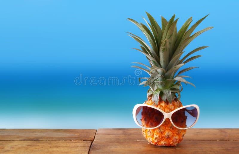 Ananas con gli occhiali da sole sulla tavola Spiaggia e tema tropicale fotografia stock