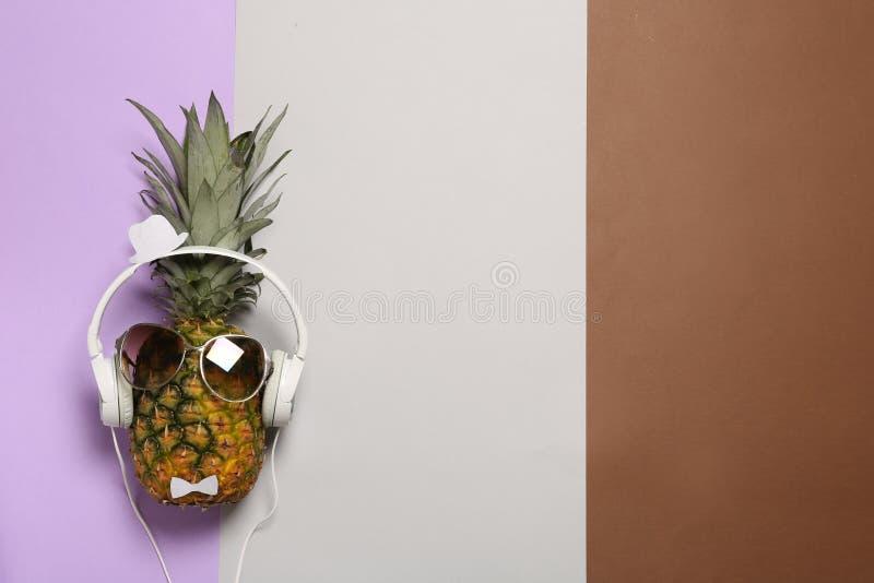 Ananas divertente con le cuffie e gli occhiali da sole sul fondo di colore, vista superiore immagine stock libera da diritti