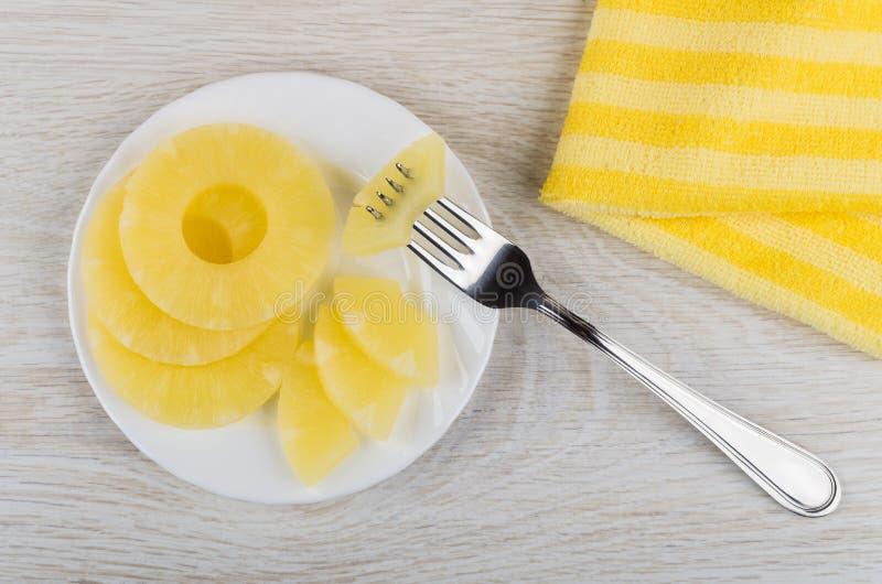 Ananas en boîte dans la soucoupe, morceau d'ananas ficelé sur la fourchette image stock
