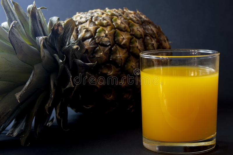 Ananas et verre de jus d'isolement sur le fond de noir foncé photos stock