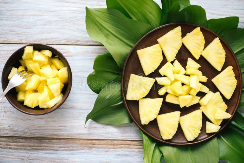 Ananas fresco affettato in una ciotola sulle foglie immagini stock