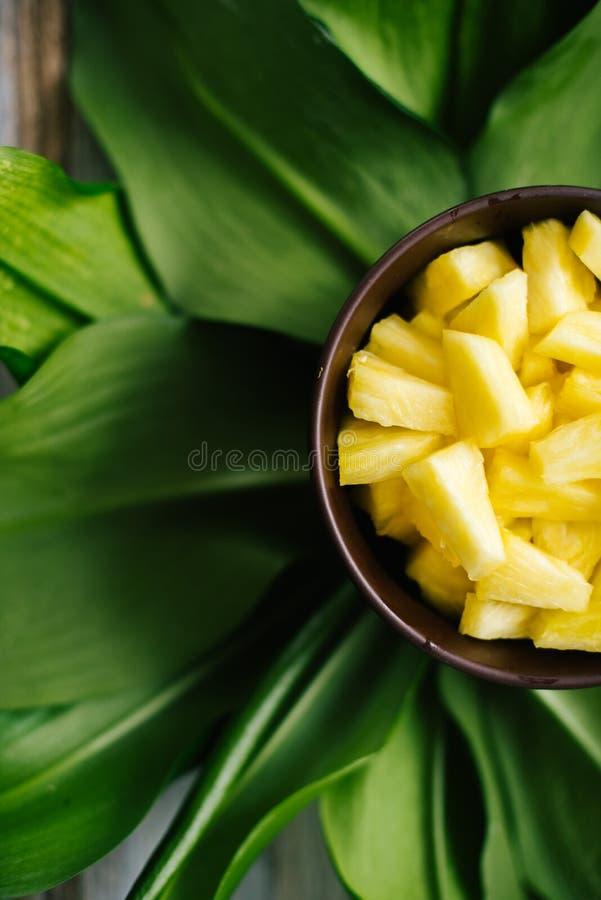Ananas fresco affettato in una ciotola sulle foglie fotografie stock libere da diritti