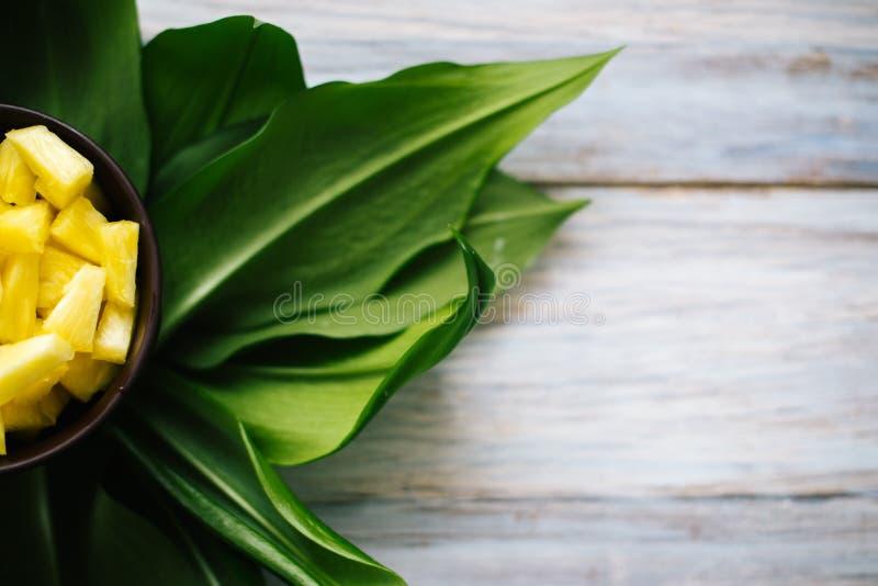 Ananas fresco affettato in una ciotola sulle foglie fotografie stock
