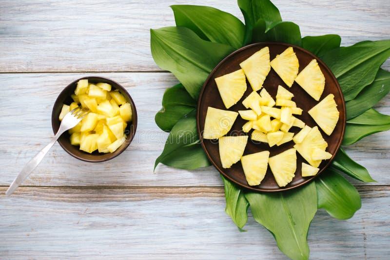 Ananas fresco affettato in una ciotola sulle foglie fotografia stock libera da diritti