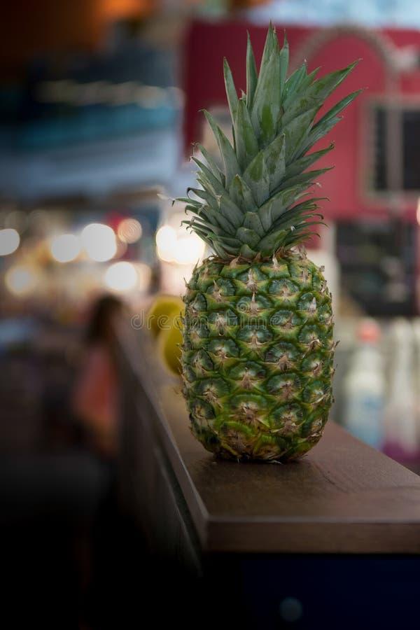 Ananas fresco isolato sullo scaffale di legno stretto rettangolare di legno scuro immagini stock libere da diritti