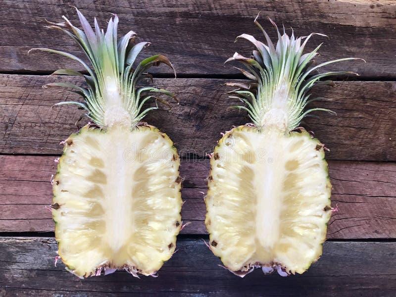 Ananas-Hälften öffnen sich auf hölzernem Hintergrund lizenzfreie stockfotografie