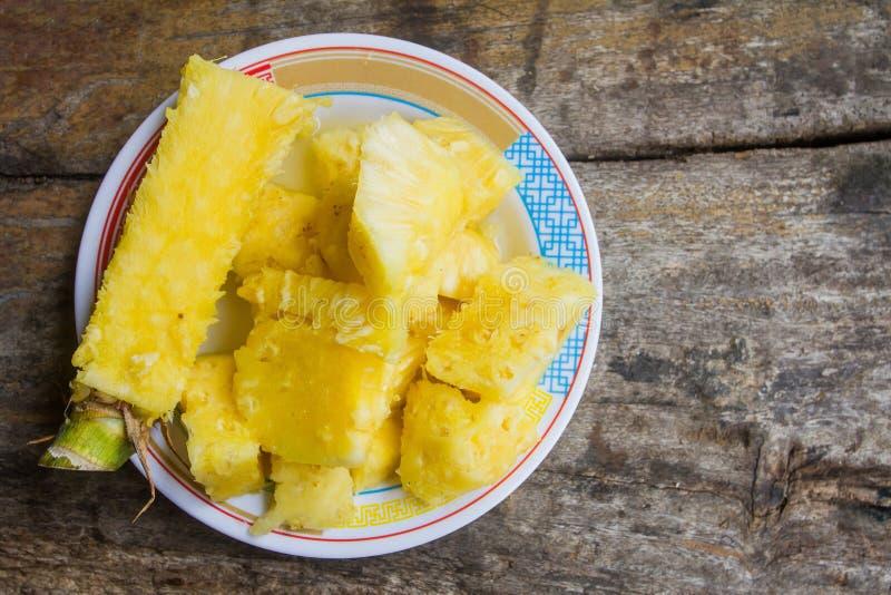 Ananas heerlijke zoete die ui, besnoeiing in stukken in een schotel op een houten lijst op de achtergrond wordt geplaatst royalty-vrije stock foto