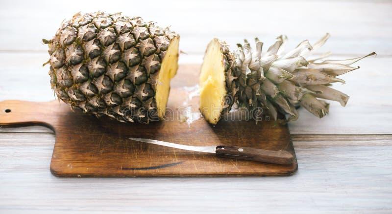 Ananas mûr bissecté mûr sur un fond en bois image stock