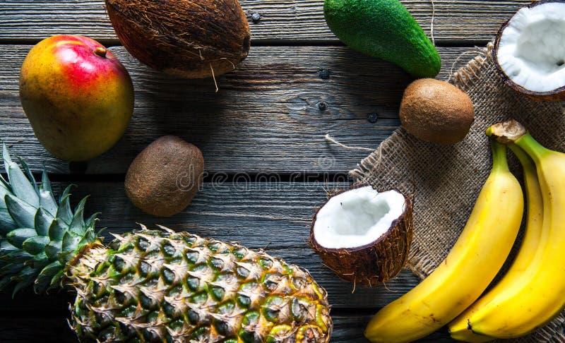 Ananas med bananen, mango, avokadot och kokosnöten på träbakgrund Frukt mat, natur royaltyfri foto